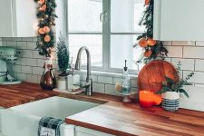 a gorgeous fresh foliage, evergreens and dried citrus slice garland farming the window brings a rustic and natural feel to the space