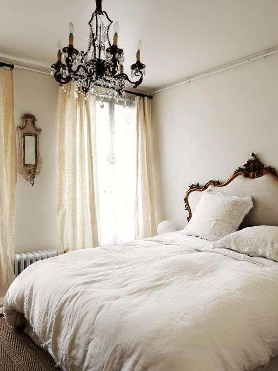 a gorgeous neutral bedroom with a chic bed with a carved headboard, a crystal chandelier, neutral textiles and mirrors is wow
