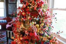 a granny chic Christmas tree with lights, ornaments and colorful pompoms on branches is a bold idea