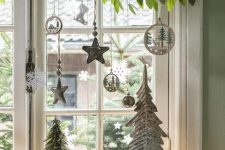 a greenery branch, silver and white whimsical ornaments and mini trees with lights for lovely and chic holiday decor