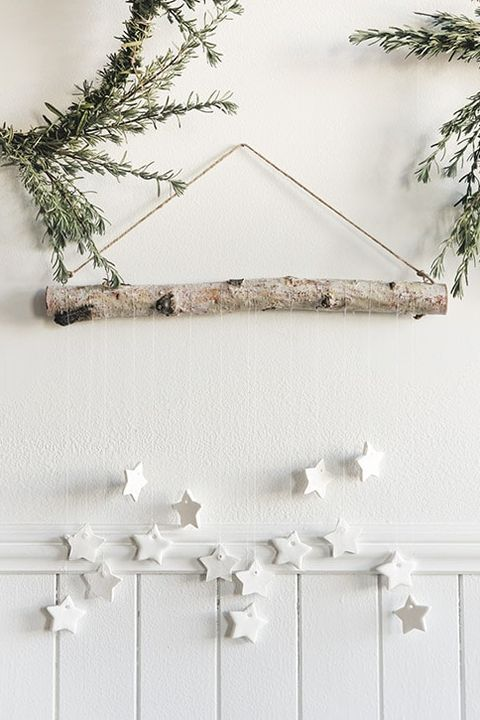 a hanging with a branch and white clay stars plus greenery around is a lovely rustic decor idea for Christmas