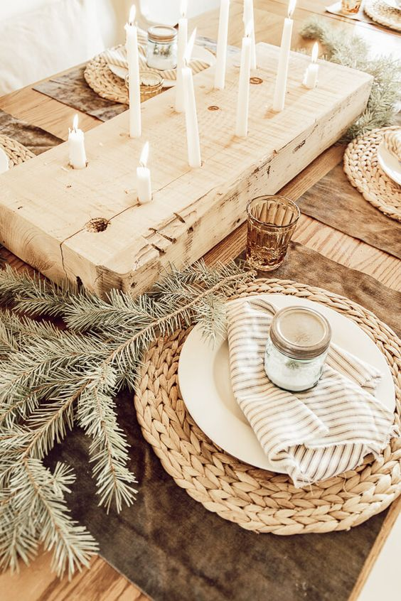 a hygge Christmas table with woven chargers, fir branches, a wooden board with candles, colored glasses is very peaceful