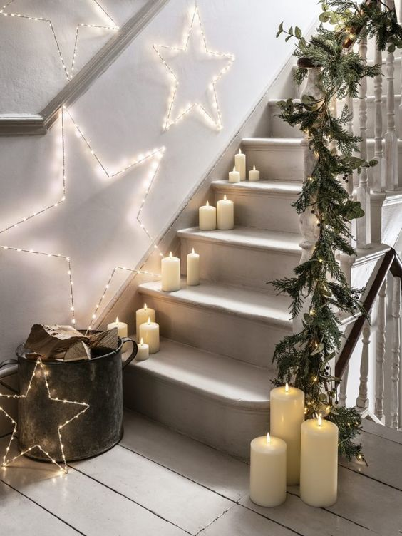 a hygge-like Christmas staircase with pillar candles, light stars over the stairs and a fir and foliage garland with lights on the rails