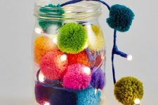 a jar with colorful pompoms and lights is a lovely decoration and table lamp for Christmas that can be DIYed