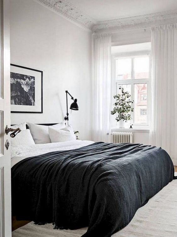 a laconic Scandinavian bedroom with a black bed, black and white bedding, black sconces, a black and white artwork and a potted plant