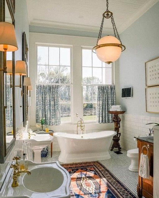 a light-filled bathroom with blue walls, a free-standing tub, mirrors with sconces, a pendant lamp and a boho rug