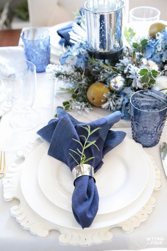 a lovely Christmas tablescape with navy linens, glasses, blooms and a candleholder, silver bells, white porcelain and chargers