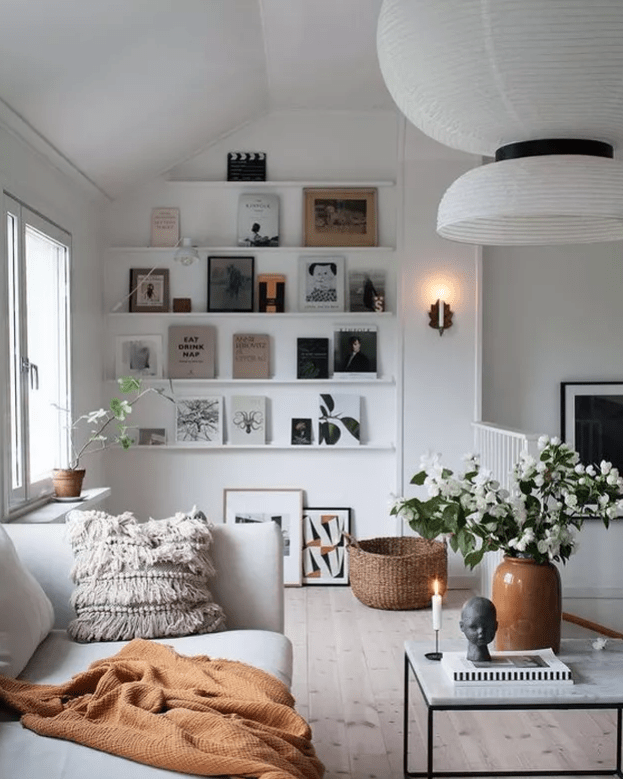 a lovely Nordic living room in neutrals, with ledges, a white sofa, paper lamps, black and white artworks and books, potted greenery and blooms