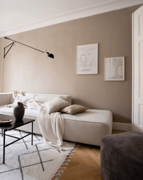 a lovely Scandinavian living room with taupe walls, a neutral daybed, a black sconce and a table plus some neutral and subtle artworks