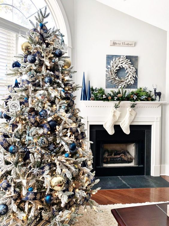 a lovely flocked Christmas tree with blue and navy ornaments, lights, silver and gold ornaments and painted ones just wows