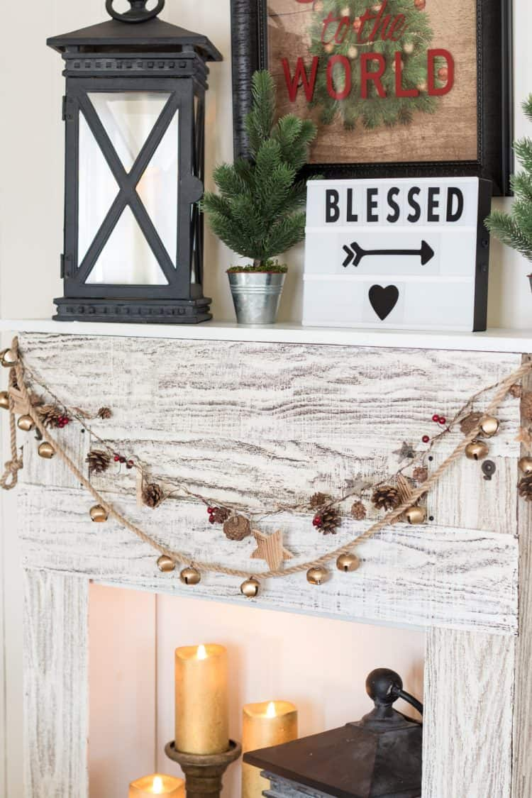 a lovely gold bell garland plus a pinecone and berry one with stars for decorating a faux rustic mantel for Christmas
