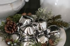 a lovely rustic Christmas centerpiece of a bowl with greenery, pinecones and silver bells is a cool last minute idea to go for