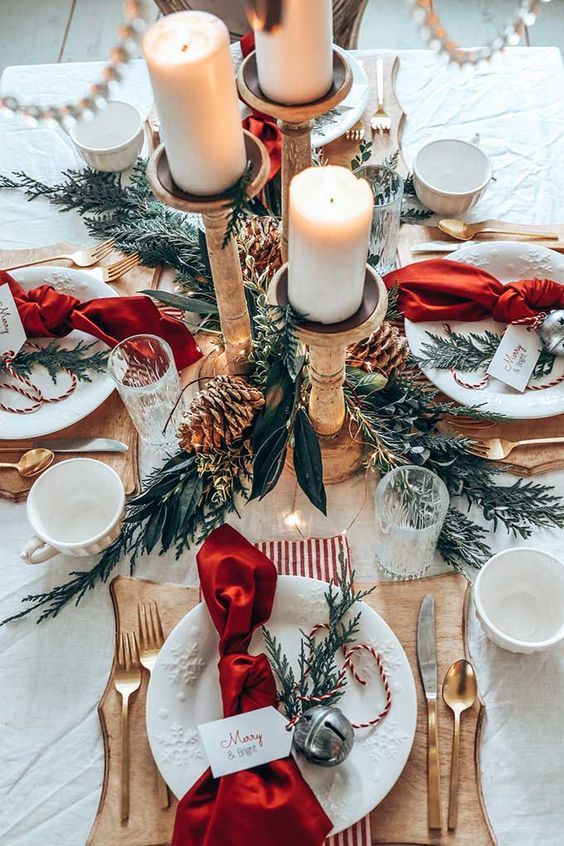 a lovely rustic Christmas table with wooden chargers, snowflake plates, wooden candleholders, greenery, pinecones and gold cutlery