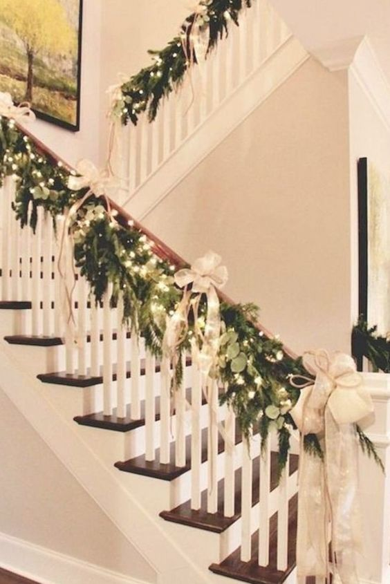 a lush greenery and fir garland with lights, neutral bows and ribbons for elegant and chic Christmas railing decor