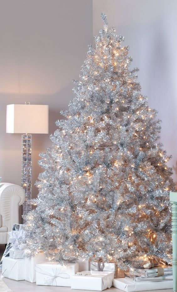 a luxurious silver Christmas tree with only lights and stacks of gift boxes is a lovely and very glam idea for any space