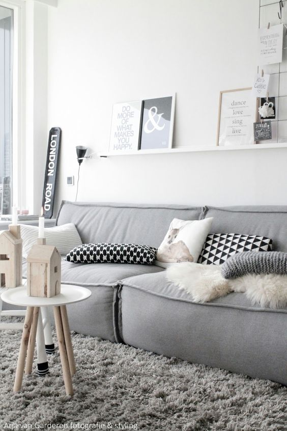 a minimal Scandinavian living room with a simple grey sofa, a ledge with artworks and a grid, a couple of stools and candles and lights