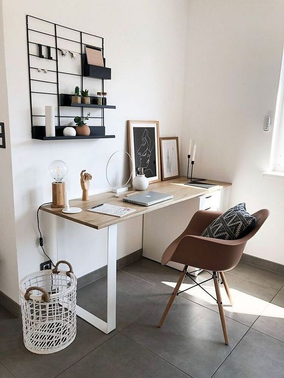 a minimalist small home office with a sleek desk, a brown chair, an open black shelf, some artworks and a basket