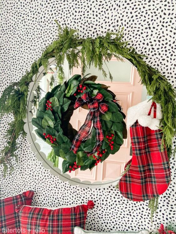 a mirror accented with a greenery, berry and plaid wreath, fir branches, a plaid stocking and plaid pillows for bright holiday decor