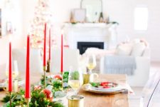 a modern Christmas tablescape with traditional touches, a fir and greenery runner, red candles, gold chargers and plaid plates, gold mugs