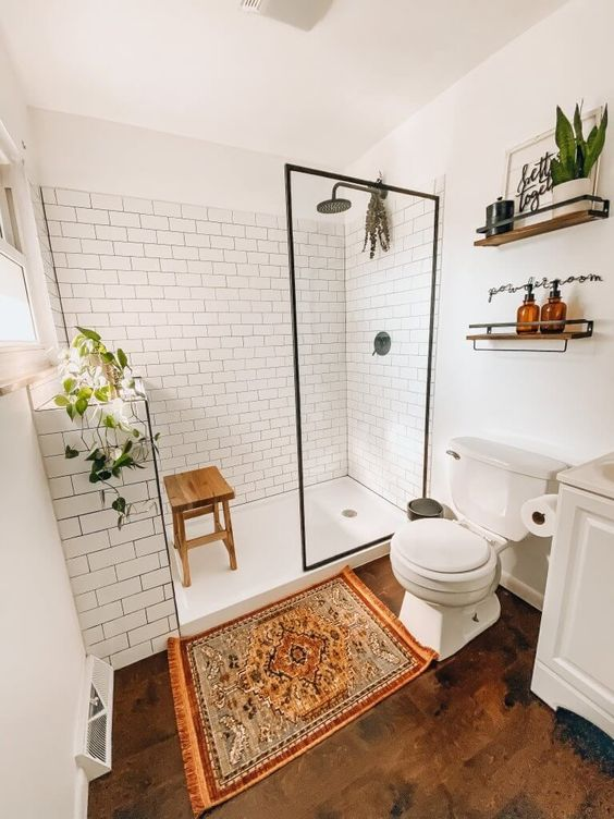 a modern farmhouse bathroom with white subway tiles, a wooden floor, white furniture, potted greenery and a boho rug