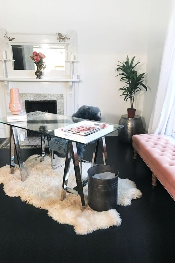 a modern feminine home office with a glass trestle desk, a pink upholstered bench, a fireplace, a white faux fur rug and potted plants