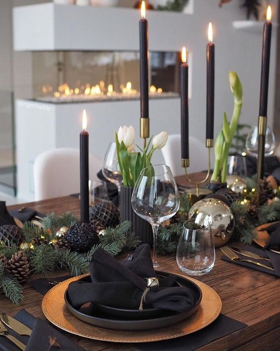 a modern moody Christmas table with gold chargers, blakc plates and napkins, black candles, white tulips and black ornaments and pinecones