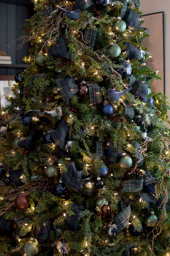 a moody Christmas tree with navy plaid ribbons, navy and green ornaments, branches, moss, greenery and pinecones is very woodland like