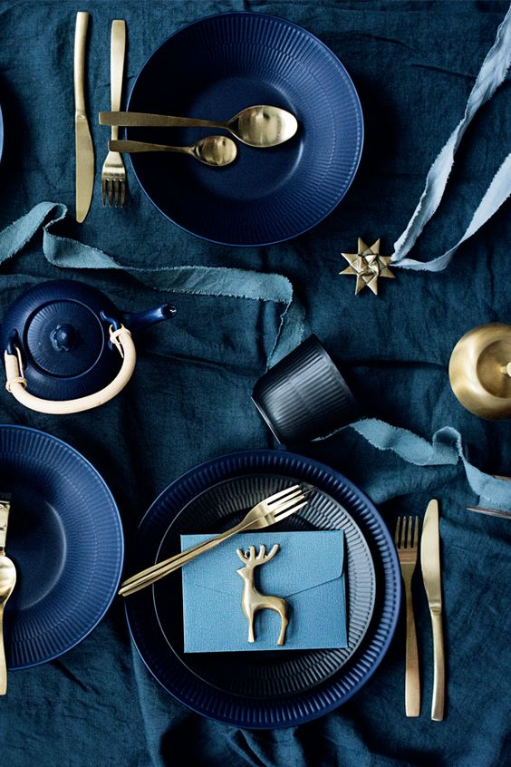 a moody blue and gold Christmas tablescape with gold cutlery, black and navy plates and blue linens for a a modern space