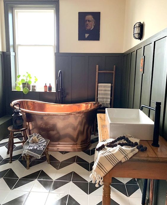 a moody vintage bathroom with green paneling, a copper tub, a wooden table as a vanity and vintage artworks