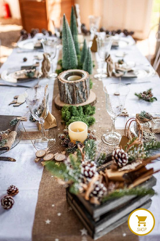a natural Christmas table setting with a burlap runner, moss, tree stumps, snowy pinecones, tinsel trees and glasses