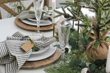 a natural Christmas table setting with greenery, fir, a Christmas tree in burlap, candles, metallic ornaments and striped napkins
