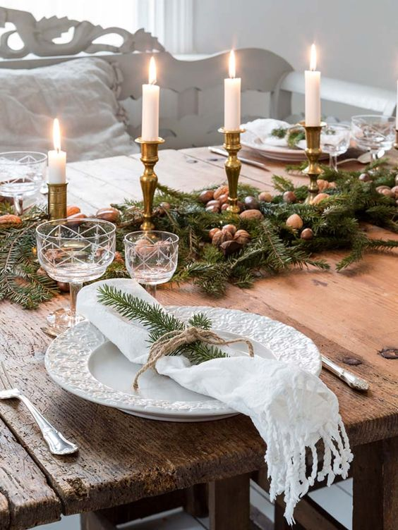 a natural Christmas tablescape with fir branches, nuts and candles in gold candleholders, beautiful plates and glasses is chic