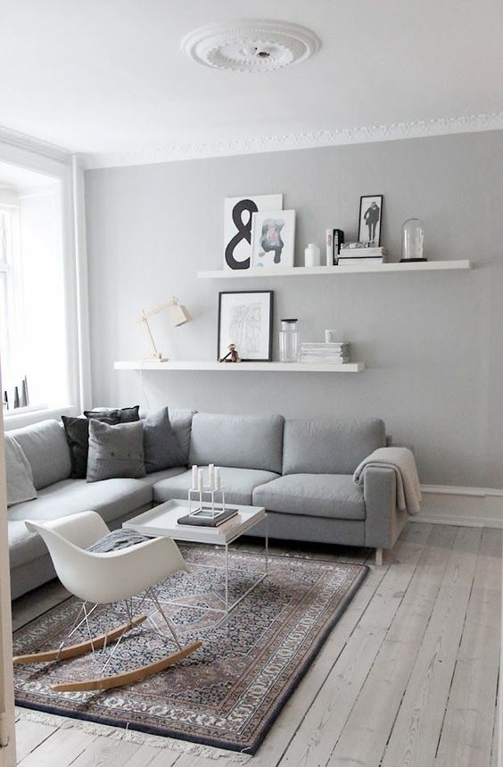 a neutral Scandi living room with a grey sectional, a couple of shelves, monochromatic pilows, a white chair and table