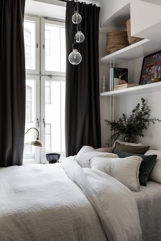 a neutral Scandinavian bedroom with open shelves, neutral bedding, a cluster of bulbs and black curtains