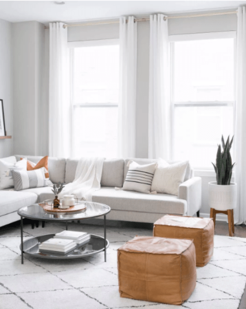a neutral Scandinavian living room with a creamy corner sofa, leather ottomans, a round table, a potted plant and white curtains