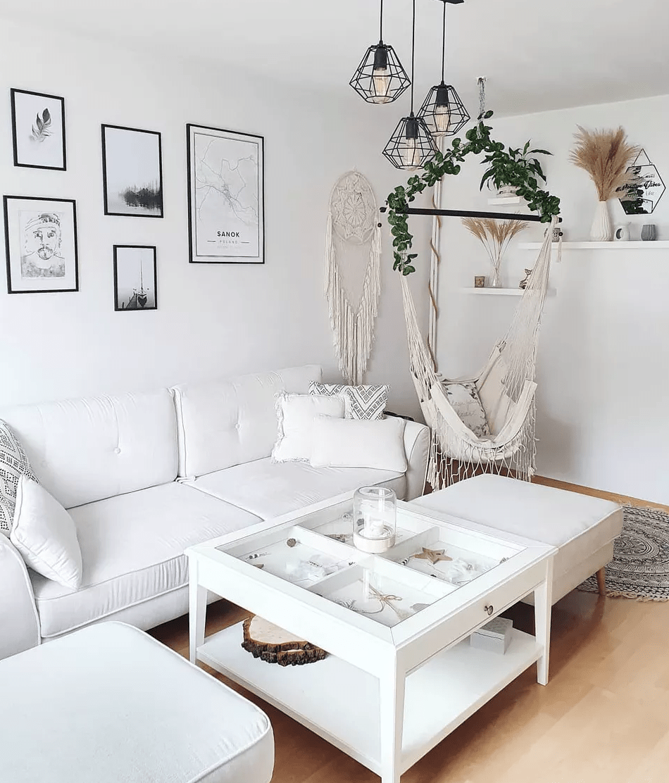 a neutral Scandinavian living room with white walls and a ceiling, white furniture, a hammock chair, some macrame and art plus pendant lamps