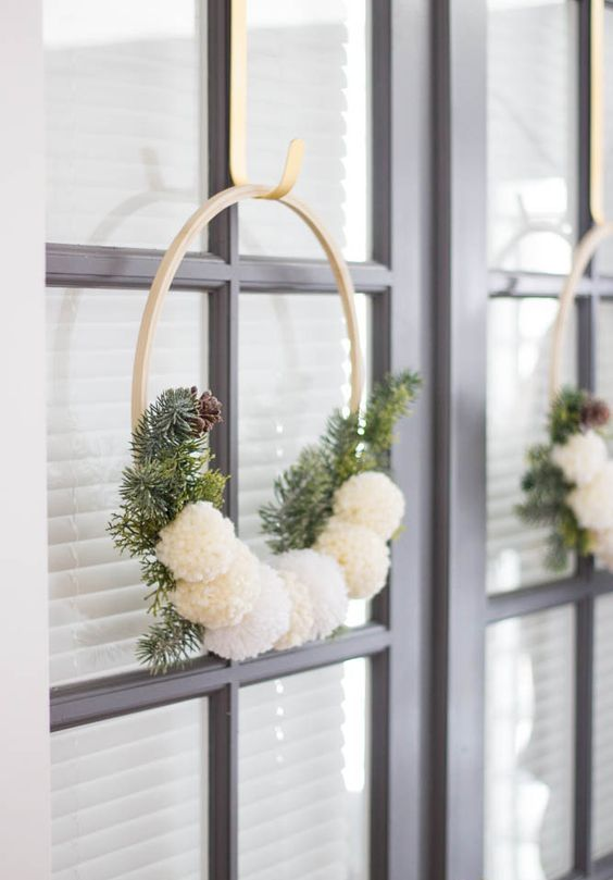 a neutral and simple Christmas wreath of an embroidery hoop, fir branches, pinecones and white pompoms is all you need