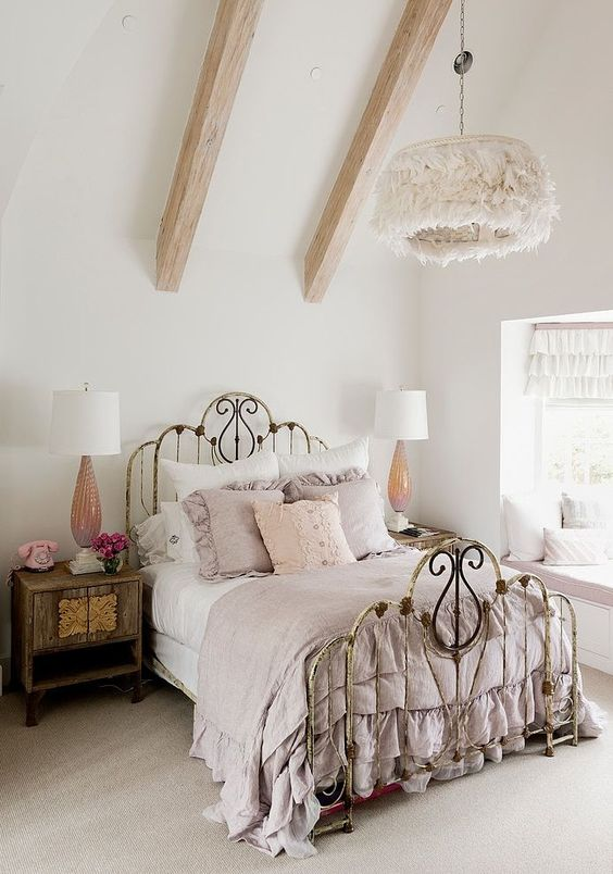 a neutral attic vintage bedroom with a shabby chic bed, pastel bedding, a fluffy chandelier, nightstands and cool lamps