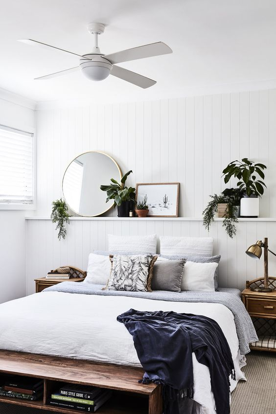 a neutral beachy bedroom with an open shelf with potted greenery, stylish wooden furniture and printed bedding
