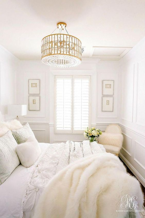 a neutral glam bedroom with chic furniture, a glam crystal chandelier, faux fur and artworks