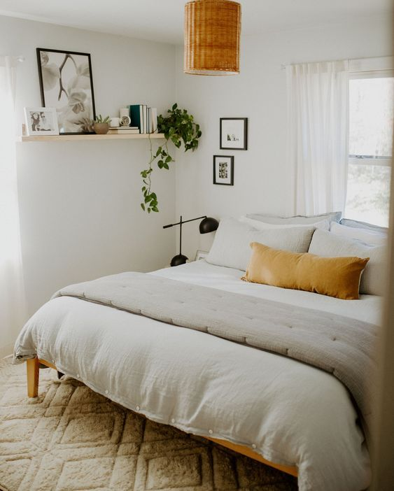 a neutral mid-century modern bedroom with simple furniture, a wicker lamp and black tble lamps, an open shelf with a potted plant