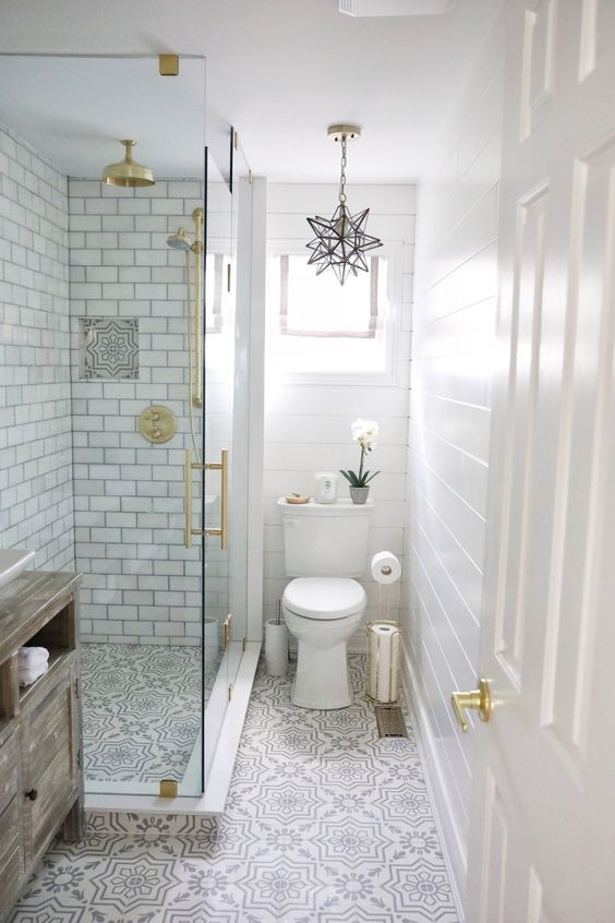 a neutral small bathroom with beadboard, printed tiles, subway tiles in the shower, gold touches and a star-shaped chandelier