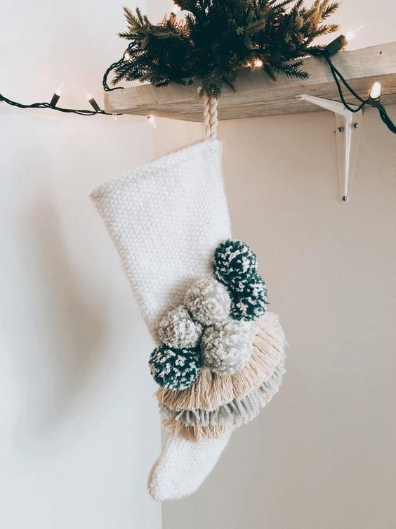 a neutral stocking with pompoms and fringe is a cool decor idea for the holidays, it will add a boho feel to your decor