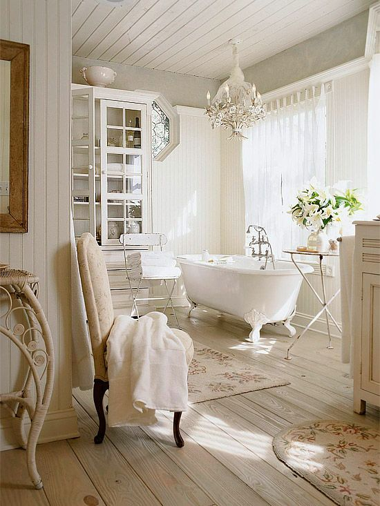 a neutral vintage bathroom with a glass cabinet, a clawfoot tub, some vintage and shabby chic furniture is veyr beautiful