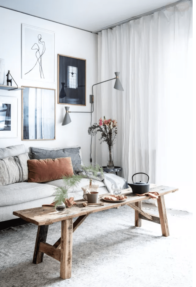 a peaceful Scandinavian living room with a grey sofa, muted color pillows, a stylish gallery wall, a wooden bench and grey sconces plus blooms