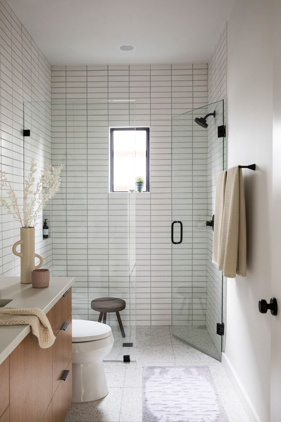 a peaceful and welcoming small bathroom clad with white skinny tiles, with a chic vanity, black fixtures and a small window in the shower