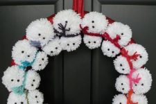 a pompom snowman wreath with colorful rope scarves is a fun front door decor idea for Christmas