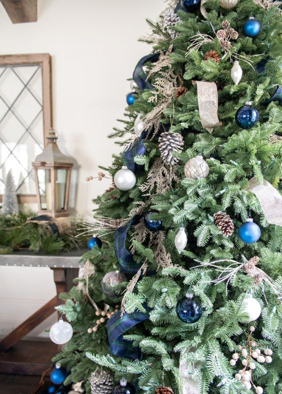 a pretty Christmas tree with silver and blue ornaments, a navy plaid ribbon, pinecones, twigs and wooden beads is very chic