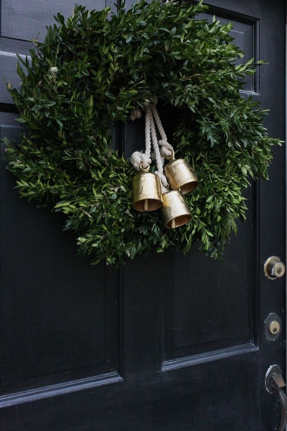 a pretty and simple Christmas wreath of greenery and gold bells on rope is a lovely and chic idea with a vintage feel