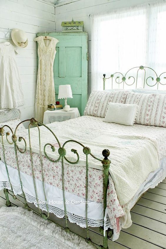 a pretty bedroom with a metal bed, a mint green door, shabby chic furniture, floral bedding and cute lamps